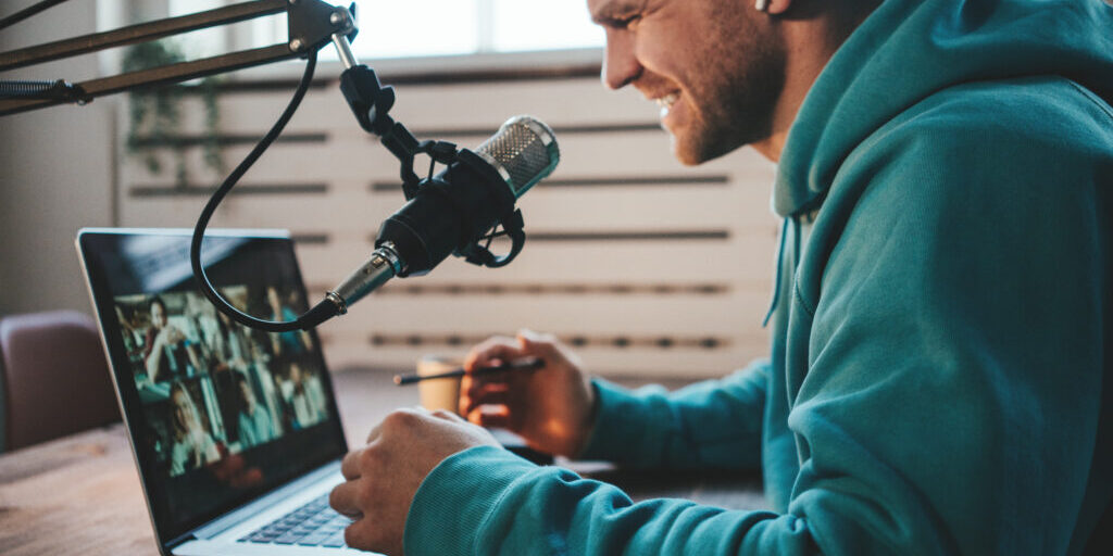 Handsome smiling host streaming his live podcast using microphone and laptop at his homemade broadcast studio